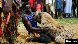 Abdullahi Jahun (24), memeluk seekor hyena dalam sirkus di Gabasawa, Negara Bagian Kano, Nigeria, 27 Juli 2021. (REUTERS/Afolabi Sotunde)