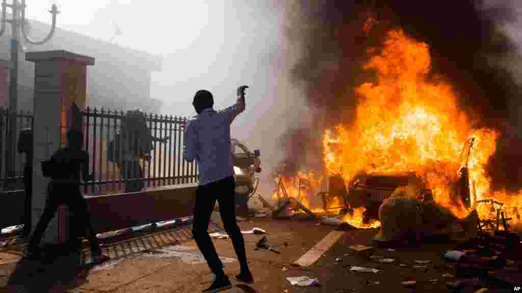 A car burns outside the parliament building in Burkina Faso as people protest against their longtime President Blaise Compaore who seeks another term in Ouagadougou, Burkina Faso, Oct. 30, 2014.