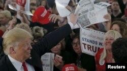 """Ứng cử viên tổng thống của Đảng Cộng hòa Donald Trump cầm một tờ báo với tiêu đề """"Clinton, Trump dẫn đầu"""" trong một buổi mít tinh ở Warwick, Rhode Island, ngày 25 tháng 4 năm 2016."""