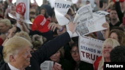 "U.S. Republican presidential candidate Donald Trump holds up a newspaper with a headline reading ""Clinton, Trump Lead"" at a campaign rally in Warwick, Rhode Island, April 25, 2016."