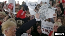 "FILE - U.S. Republican presidential candidate Donald Trump holds up a newspaper with a headline reading ""Clinton, Trump Lead"" at a campaign rally in Warwick, Rhode Island, April 25, 2016."