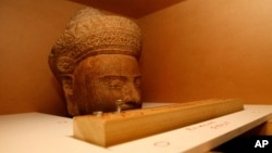 The 10th-century Cambodian sandstone statue form the Metropolitan Museum of Art in New York is seen in a box during a handover ceremony, at Phnom Penh International Airport, Phnom Penh, Cambodia, Tuesday, June 11, 2013.