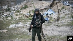 A Libyan rebel fighter carries a heavy machine gun in the besieged city of Misrata, Libya, April 23, 2011