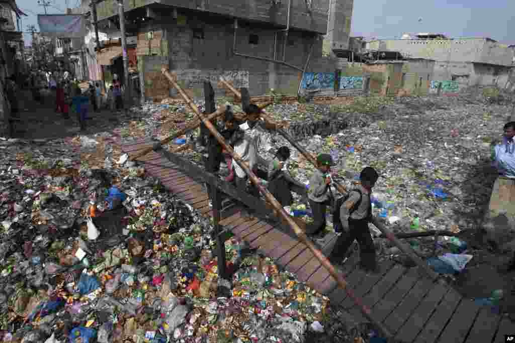 School children cross a makeshift pedestrian bridge over a drain covered with garbage at a slum in Karachi, Pakistan.