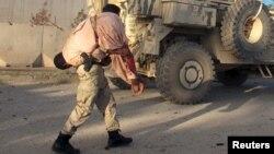 Un homme assurant la sécurité porte un homme blessé après une attaque à Lashkar Gah, dans la province de Helmand, Afghanistan, le 15 novembre 2015.