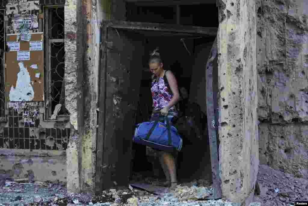A woman walks out of a damaged multi-story block of flats carrying her belongings following what locals say was recent shelling by Ukrainian forces, in central Donetsk, July 29, 2014.