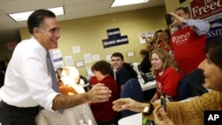 Republican presidential candidate Mitt Romney greets campaign workers during a visit to a voter call center in Green Tree, Pennsylvania, November 6, 2012.