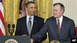 President Barack Obama stands with former President George H.W. Bush, as he prepares to present him with a 2010 Presidential Medal of Freedom during a ceremony in the East Room of the White House in Washington, February 15, 2011
