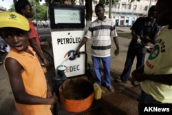 People buy kerosene for cooking and lighting at a gas station in Sao Tome, the capital of Sao Tome & Principe in West Africa's Gulf of Guinea, Nov. 4, 2006.
