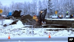 A dump truck and excavator work to repair a collapsed road in Anchorage, Alaska after an earthquake struck November 30, 2018. (AP Photo/Dan Joling)