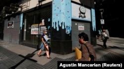 """Pedestrians walk past out-of-business stores which display """"For rent"""" signs, near the Buenos Aires' Obelisk, Argentina April 6, 2021. (REUTERS/Agustin Marcarian)"""