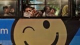 Penumpang menaiki bus dalam kota yang dihiasi dengan iklan dari sebuah situs toko online di Jakarta pada 7 Maret 2014. (Foto: AP/Dita Alangkara)