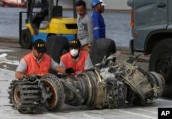 ARSIP – Para petuga memeriksa mesin pesawat yang berhasil diangkat dari lokasi jatuhnya Lion Air di Jakarta, Indonesia, 4 November 2018