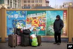 2018年2月9日,一名男子站在北京火车站外面的一堆行李旁边,准备回家过春节。旁边是种种宣传口号。