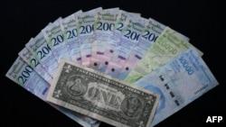 Imagen de un billete de un dólar y su equivalente promedio en la divisa venezolana (32.000 bolívares).