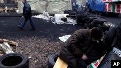 Những người biểu tình chống ông Yanukovych ngủ tại một hàng rào chướng ngại do họ dựng lên tại Quảng trường Độc lập, 28/2/14