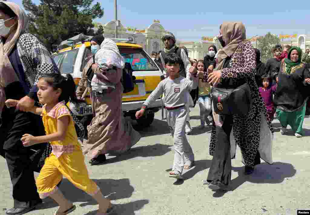 Women with their children try to get inside Hamid Karzai International Airport in Kabul, Afghanistan.