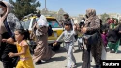 带着孩子的妇女试图进入喀布尔的哈米德·卡尔扎伊国际机场。(2021年8月16日)