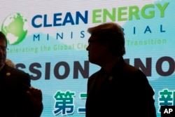 """U.S. Energy Secretary Rick Perry is silhouetted near the words """"Clean Energy"""" during a photo session after the opening ceremony of an international clean energy conference in Beijing."""