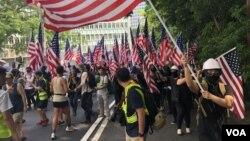 Para pengunjuk rasa berpawai sambil mengibarkan bendera AS di Hong Kong. (Foto: Iris Tong/VOA)