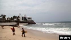 FILE - Surfers walk along a closed beach ahead of Hurricane Blanca in Mazatlan, state of Sinaloa, Mexico.