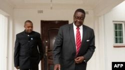 Peter Mutharika, candidat du Parti démocrate-progressiste (DPP) du Malawi aux élections présidentielles, quitte sa maison flanquée de son compatriote Saulos Chilima, à Blantyre, le 25 mai 2014.