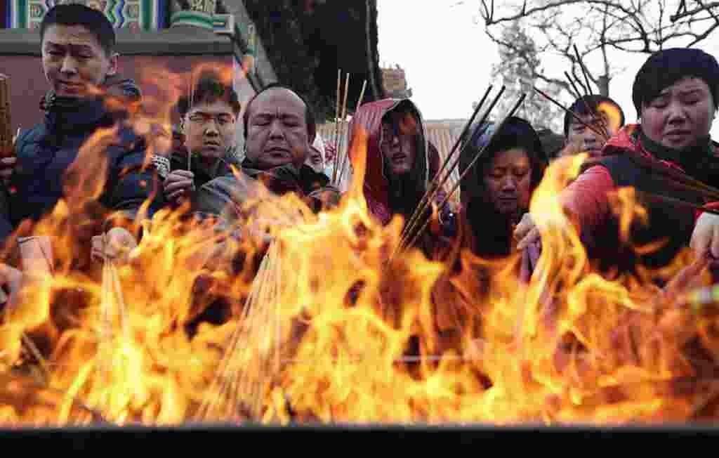 Warga membakar dupa pada hari pertama Imlek di kuil Yonghegong Lama di Beijing. Tahun Baru Imlek, atau Festival Musim Semi, dimulai pada 23 Januari dan menandai awal Tahun Naga (Reuters).