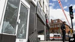 Smashed glass doors and windows and wrecked shutters of a betting shop and a jewelry shop in Enfield, north London, Aug. 8, 2011