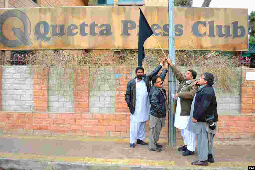 Journalists hold a black flag outside the Quetta Press Club to mourn the three journalists killed in the January 10th explosions in the city, Quetta, Pakistan, January 11, 2013.