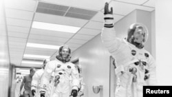 FILE - Apollo 11 astronaut Neil Armstrong waves to well-wishers on the way out to the transfer van, Cape Canaveral, Florida, July 16, 1969. Mike Collins and Buzz Aldrin follow Armstrong down the hallway.