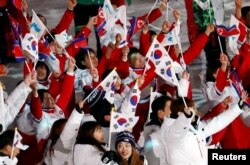 FILE - Athletes from North Korea and South Korea celebrate during the closing ceremony at the Pyeongchang 2018 Winter Olympics.