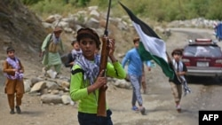 Children of local Afghan residents carrying hunting rifles and a flag walk through a road in Bandejoy area of Dara district in Panjshir province on August 21, 2021, days after the Taliban stunning takeover of Afghanistan. (Photo by Ahmad SAHEL ARMAN…