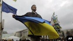 Un manifestante ondea la enseña nacional de Ucrania en la Plaza de la Independencia, en Kiev.