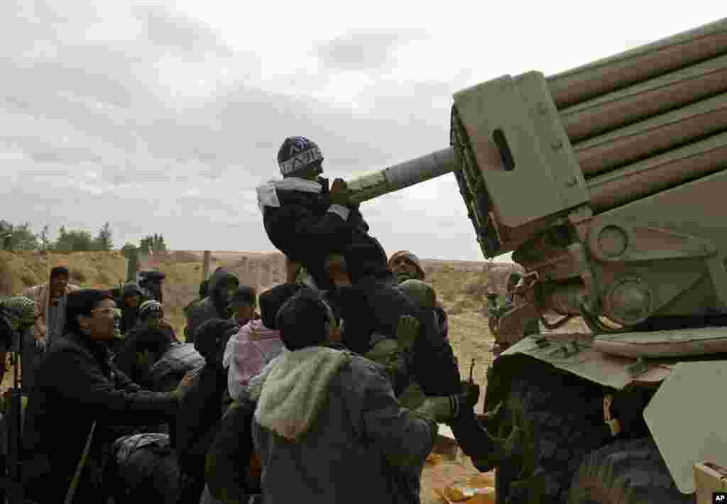 Rebel fighters load a multiple rocket launcher during a battle on the road between Ras Lanuf and Bin Jawad, March 9, 2011. (Reuters Image)