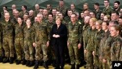 La chancelière allemande Angela Merkel pose pour une photo de groupe avec des soldats lors d'une visite du service médical de l'armée allemande à Leer, nord de l'Allemagne, lundi 7 décembre 2015.