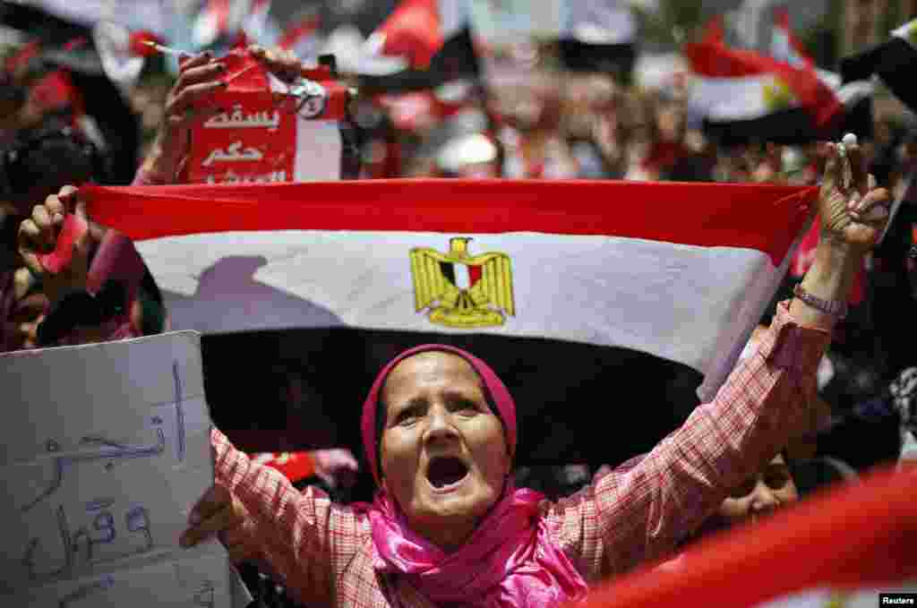 A protester, opposing Egyptian President Mohamed Morsi, holds up Egypt's flag during a protest demanding that Morsi resign at Tahrir Square in Cairo, July 2, 2013.