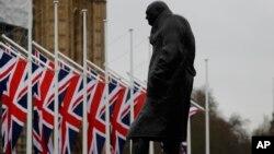 Bendera Inggris berkibar di depan Parlemen dekat patung Winston Churchill di London, 30 Januari 2020.