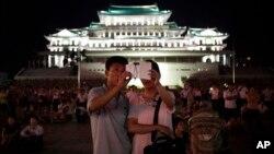 지난해 7월 평양에서 한국전 정전 61주년 기념 행사가 열린 가운데, 한 커플이 불꽃놀이를 배경으로 스마트폰 사진을 찍고 있다.