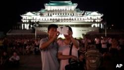 지난 7월 27일 평양에서 한국전 정전 61주년 기념 행사가 열린 가운데, 한 북한 커플이 불꽃놀이를 배경으로 스마트폰 사진을 찍고 있다.