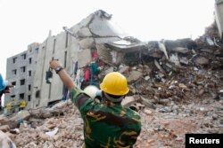 FILE - A rescue worker attempts to find survivors in the rubble of the collapsed Rana Plaza building near Dhaka, April 30, 2013.