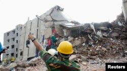 A rescue worker attempts to find survivors from the rubble of the collapsed Rana Plaza building in Savar, Bangladesh, April 30, 2013.