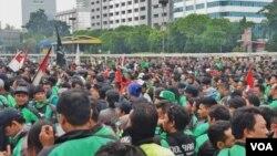 Ratusan pengemudik ojek online berunjuk rasa di depan gedung DPR/MPR Senayan, Jakarta, hari Senin (23/4). (VOA/Fathiyah)