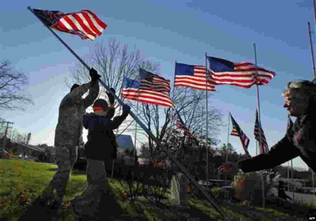 Chief Master Sgt. Bill Ross, a 35-year Air Force veteran, left, and Boy Scout Liam Gallagher, 12, raise one of 50 casket flags honoring local veterans, Thursday, Nov. 11, 2010, in Freeport, Maine. Glee Robinson Ross, right, helps guide the pole. (AP Photo
