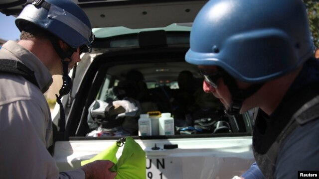 U.N. chemical weapons experts put samples collected from one of the sites of an alleged chemical weapons attack in their vehicle, in the Ain Tarma neighborhood of Damascus, Aug. 28, 2013.