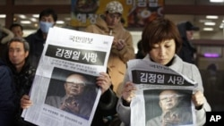 """South Koreans read about the death of North Korean leader Kim Jong Il at a Seoul train station on Monday, Dec. 19, 2011. The headline reads """"The death of North Korean leader Kim Jong Il."""""""