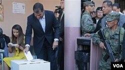 Presiden Ekuador Rafael Correa (tengah) memberikan suaranya dalam referendum di Quito, Sabtu (7/5).