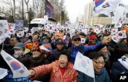 Supporters of impeached South Korean President Park Geun-hye shout slogans during a rally opposing her impeachment in Seoul, South Korea, Dec. 24, 2016.