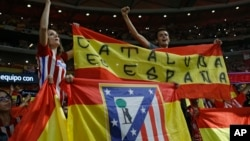 "Atletico Madrid supporters hold up a Spanish flag reading: ""Catalonia is Spain"" during a Spanish La Liga soccer match between Atletico Madrid and Barcelona at the Metropolitano stadium in Madrid, Spain, Oct. 14, 2017."