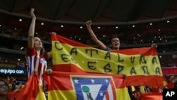 """Partidarios del Atlético de Madrid, sostienen una bandera española que dice: """"Cataluña es España"""" durante un partido de fútbol de la Liga española entre el Atlético de Madrid y Barcelona en el estadio Metropolitano de Madrid, España, el 14 de octubre de 2017."""
