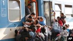 Migrantes luchan por abordar un tren en la estación de Keleti en Budapest.